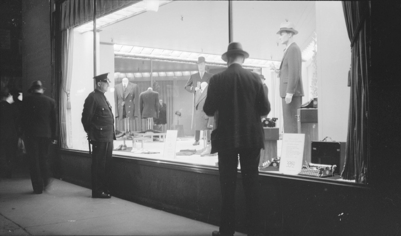 A police officer an a man peer at night into the brightly lit menswear display window at the Simpsons department store in downtown Montreal