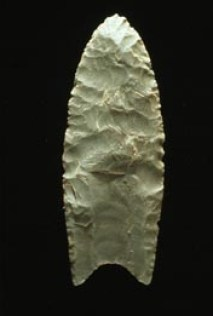 """""""A Clovis blade with medium to large lanceolate spear-knife points. Side is parallel to convex and exhibit careful pressure flaking along the blade edge. The broadest area is near the midsection or toward the base. The base is distinctly concave with a characteristic flute or channel flake removed from one or, more commonly, both surfaces of the blade. The lower edges of the blade and base is ground to dull edges for hafting. Clovis points also tend to be thicker than the typically thin later stage Folsom points. Length: 4–20 cm/1.5–8 in. Width: 2.5–5 cm/1–2"""