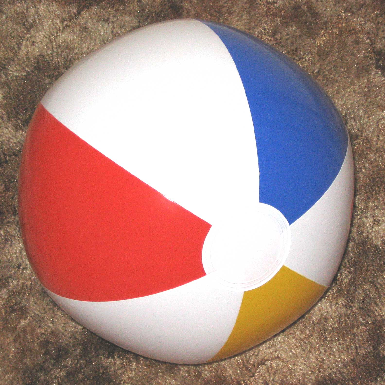 A beach ball with red, yellow, blue, and white stripes