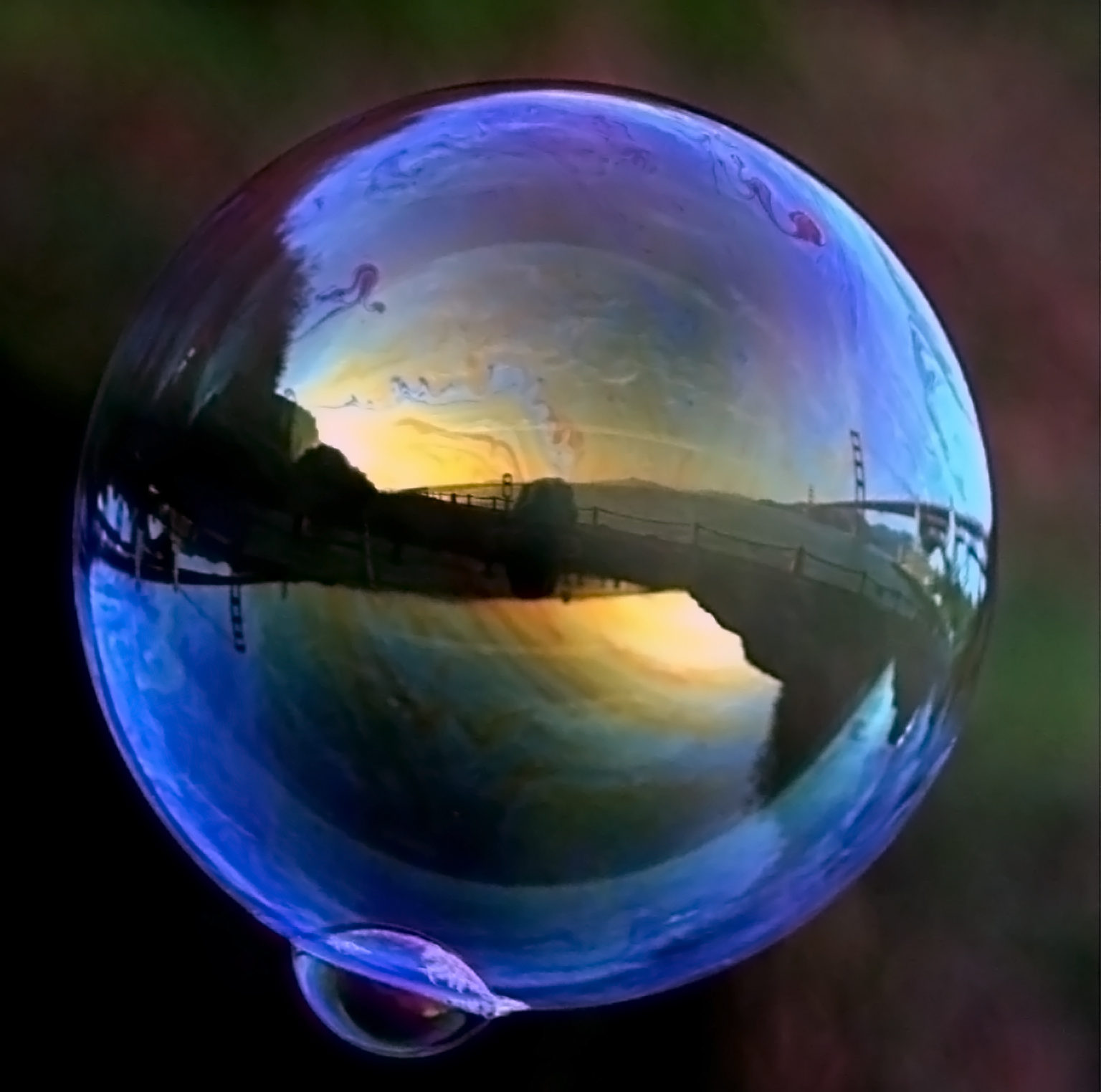 Golden Gate Bridge is reflected in a soap bubble