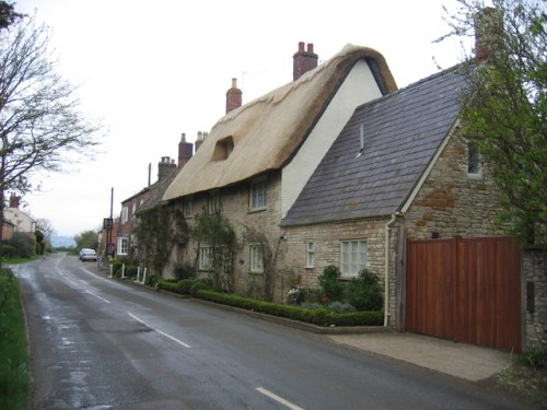 Armscote The road through the centre of the village towards Illmington with a recently thatched cottage near the Manor.