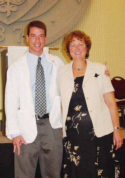 The same man seen in the infobox, here shown smiling with his teeth showing wearing a white doctor's coat over a shirt and tie, standing on the left of a smiling older woman with red hair and rosy cheeks wearing a black print dress with a pale yellow jacket. Behind them is a tage with a portion of a large seal visible
