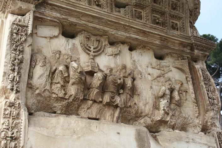 Détails de l'arc de Titus à Rome, sur ce panneau sont représentés certains des objets pris lors du sac du Temple d'Hérode, on distingue notamment le Chandelier à sept branches.