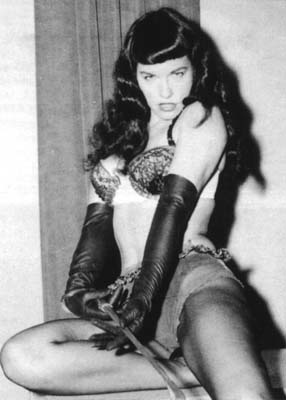 Bettie Page with a riding crop