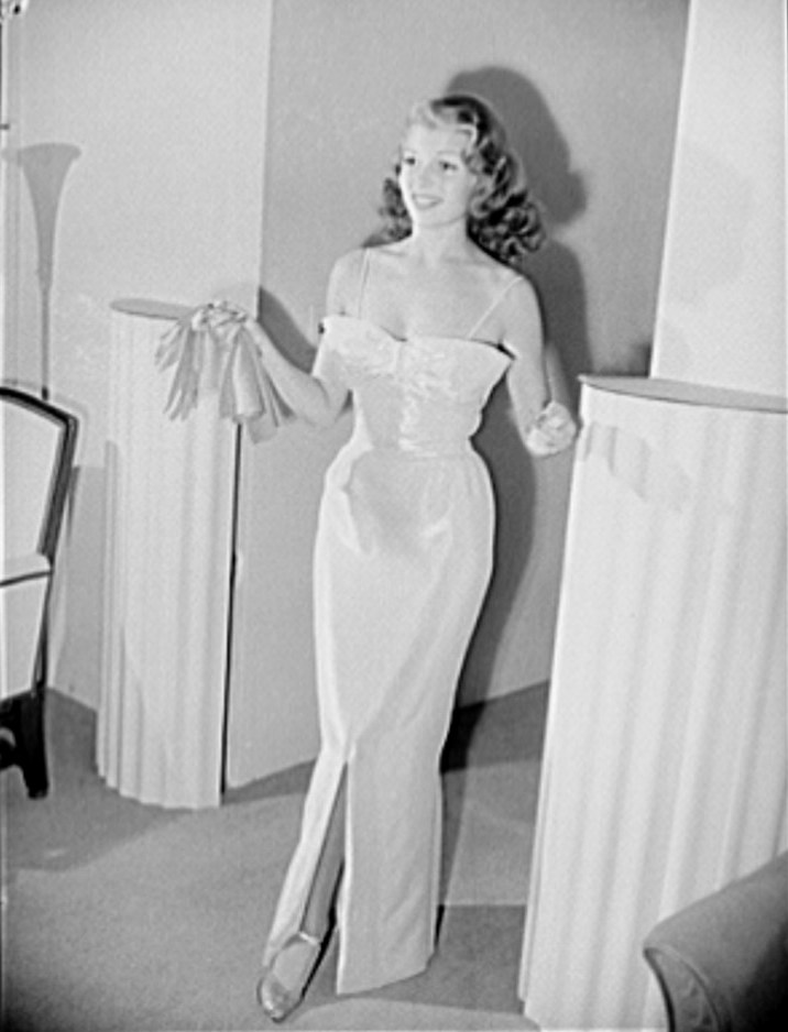 Rita Hayworth in a pink and silver lame evening dress designed by the famed Hollywood designer Howard Greer.
