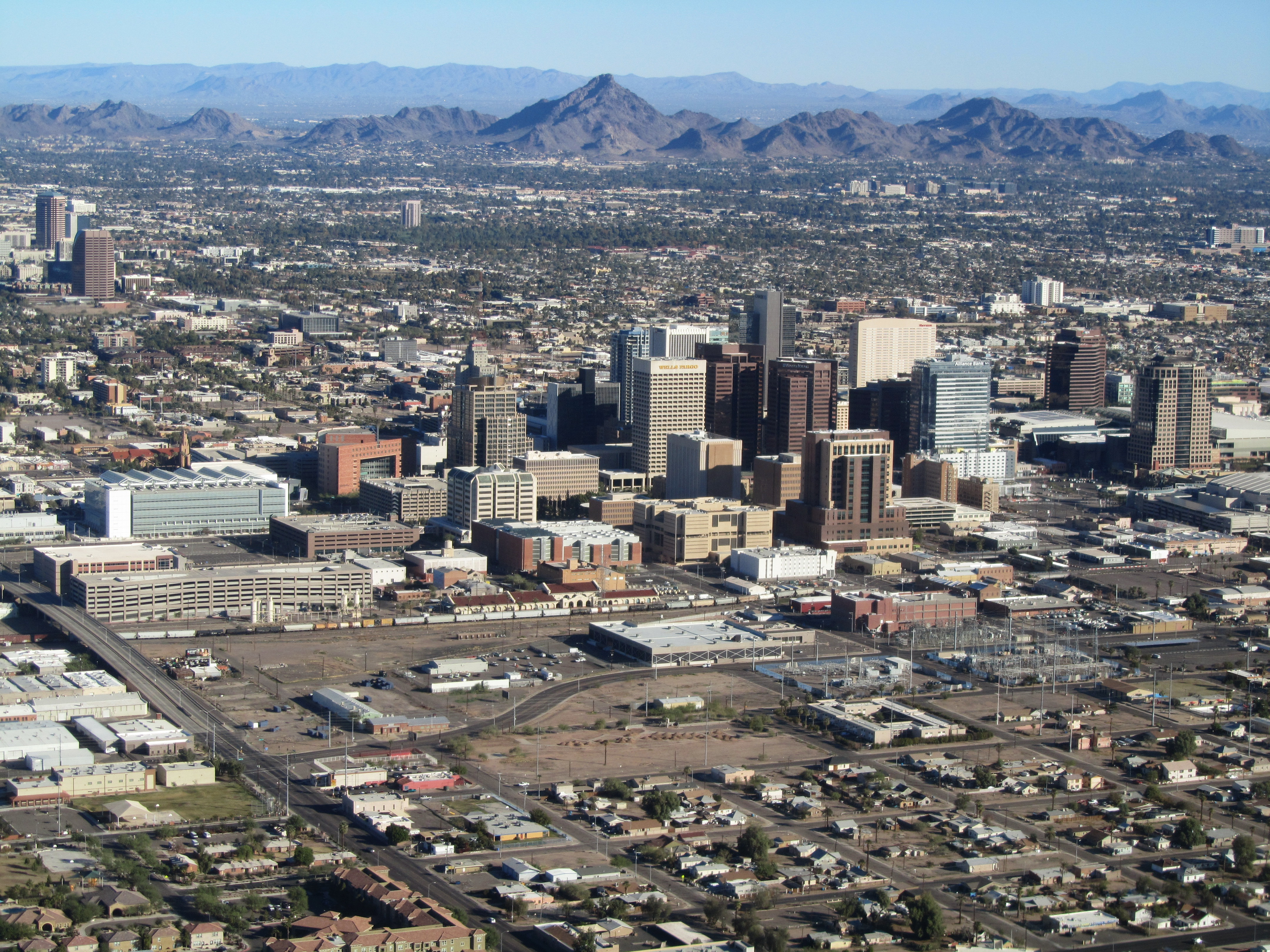 photo taken from an aircraft showing the tall buildings of downtown phoenix with the mountains