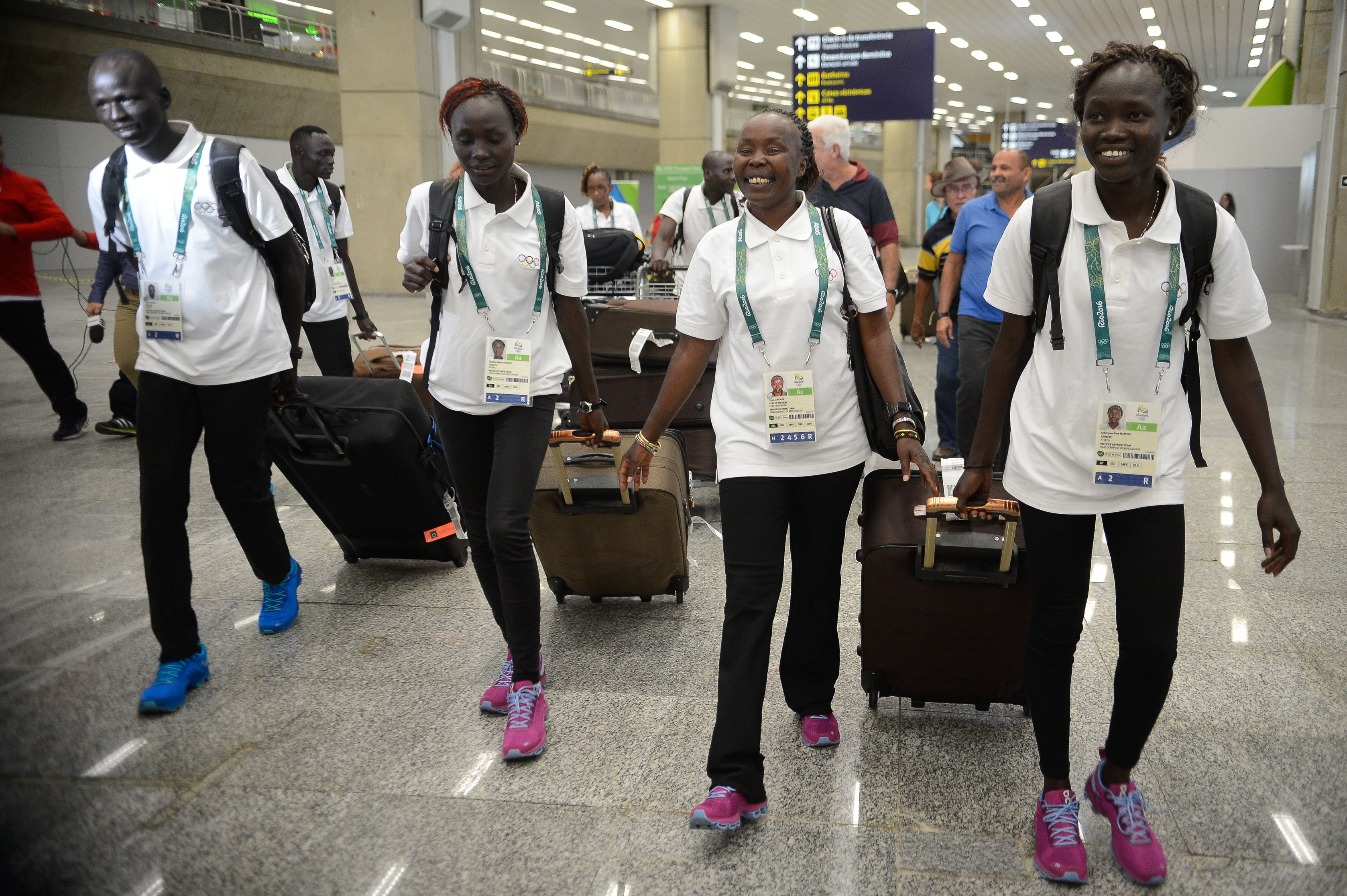 Refugee athletes at the Rio 2016 Olympics. They are standing in a line in an airport, wheeling suitcases and smiling.