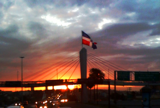 Español: Amanecer tras la bandera dominicana y...