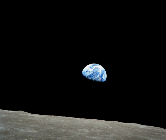 The Small Blue White Semicircle Of Earth Almost Glowing With Color In The Blackness