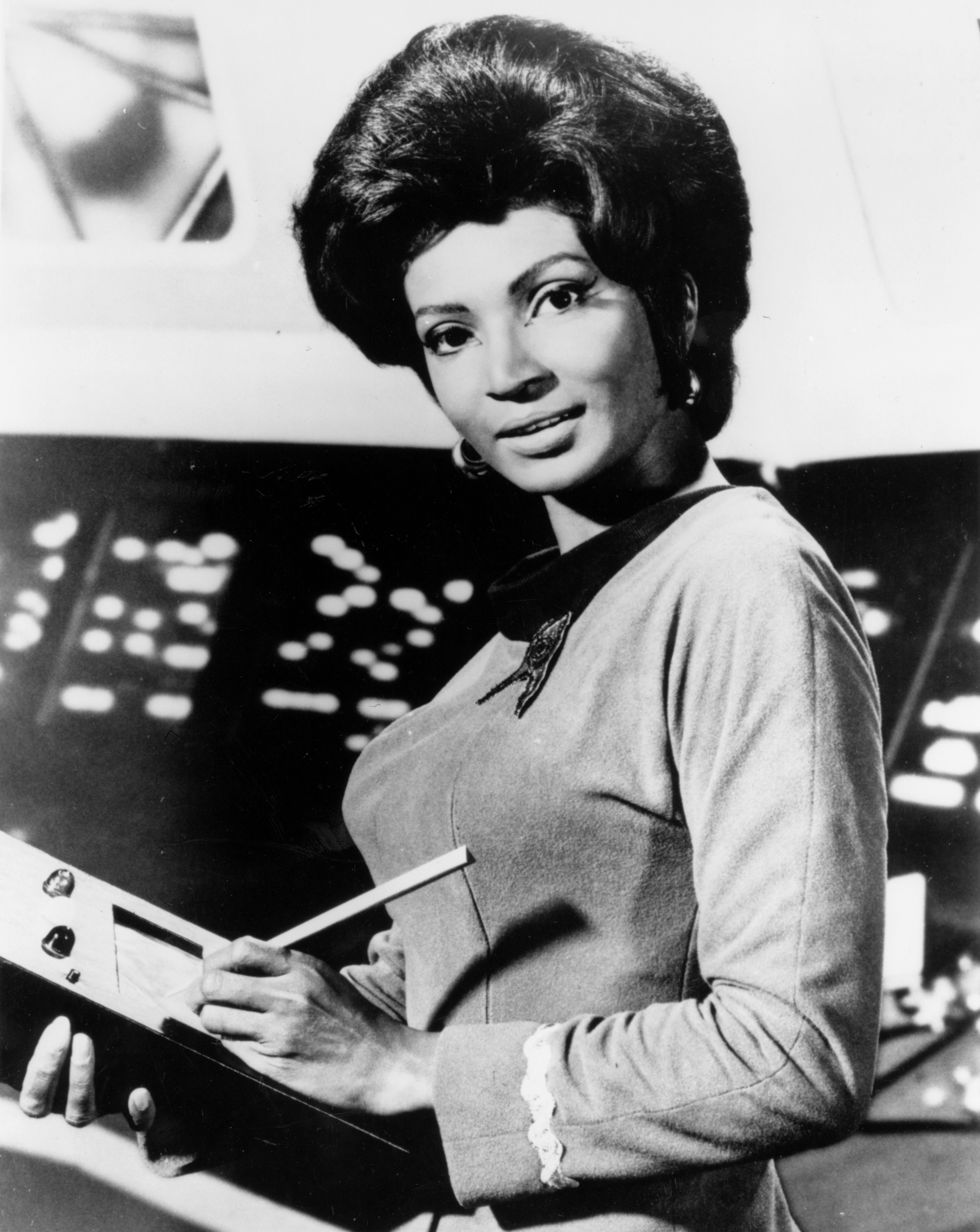 A black and white picture of Nichell Nichols as Uhura on the set of the original Star Trek.