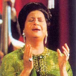 A photo for Umm Kulthum singing on a stage.