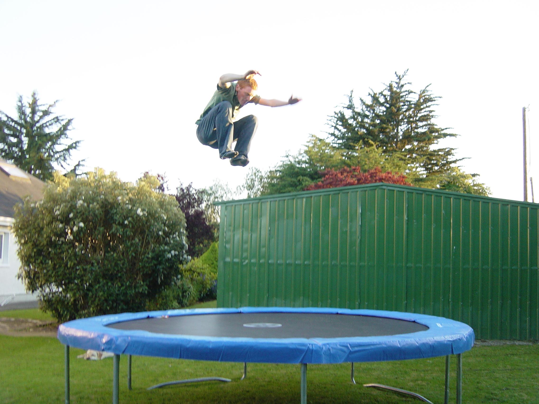 De man springt op de trampoline.