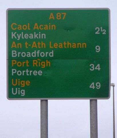 A Scottish sign using the Transport typeface on the Isle of Skye, with placenames given in both Scots Gaelic and English, and distances shown in miles.