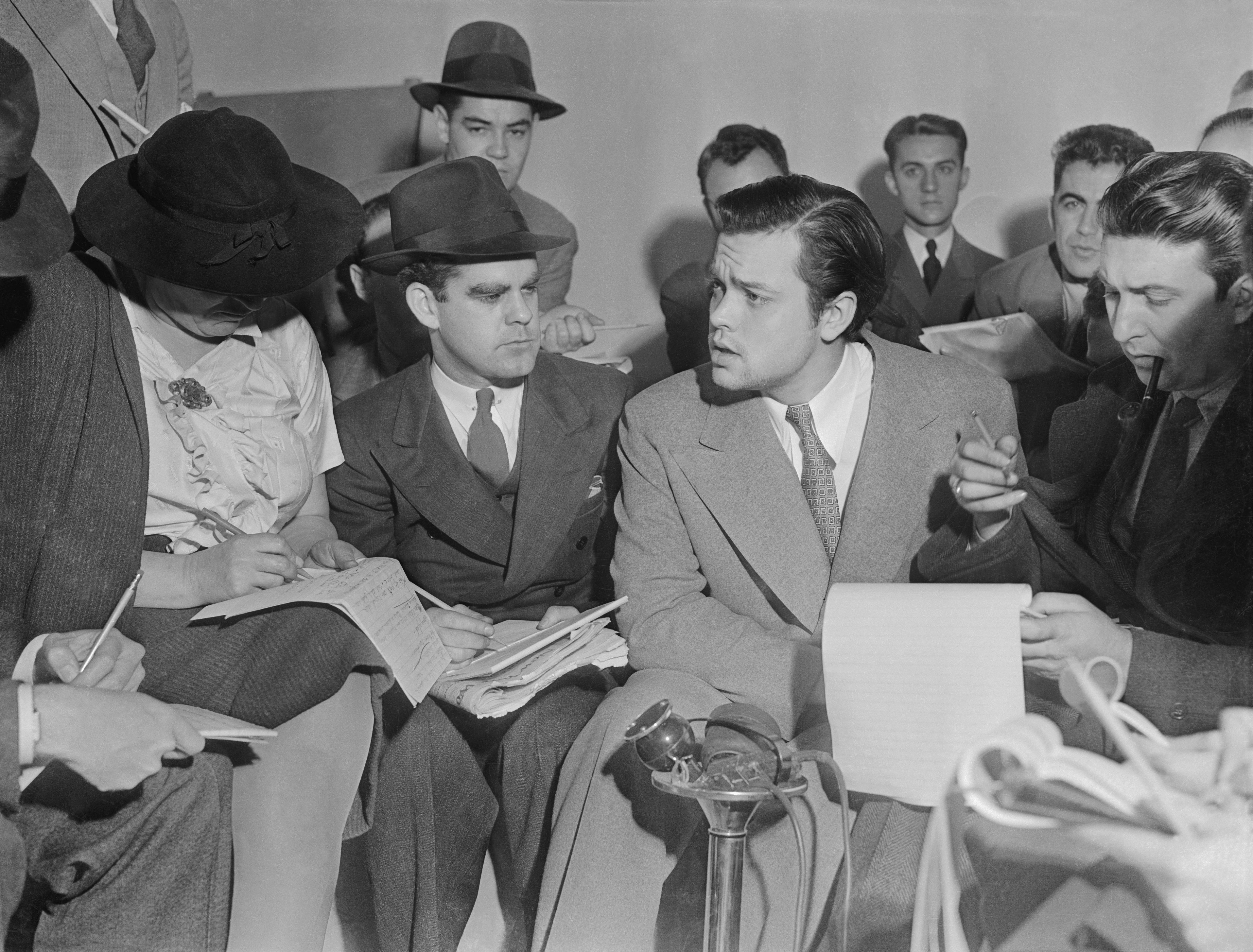 A profile of Orson Welles' face surrounded by reporters in a black-and-white photo