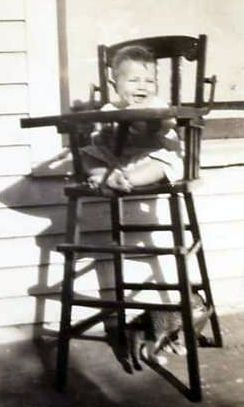 English: Baby in antique wooden high chair
