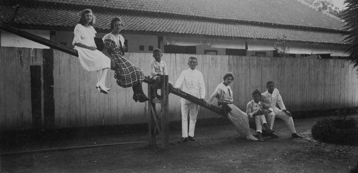 COLLECTIE TROPENMUSEUM Portret van een aantal volwassenen en kinderen van een bevriende Europese en Indo Europese familie op een wip TMnr 60046184 Mainan Bocah Belanda VS Mainan Bocah Pribumi