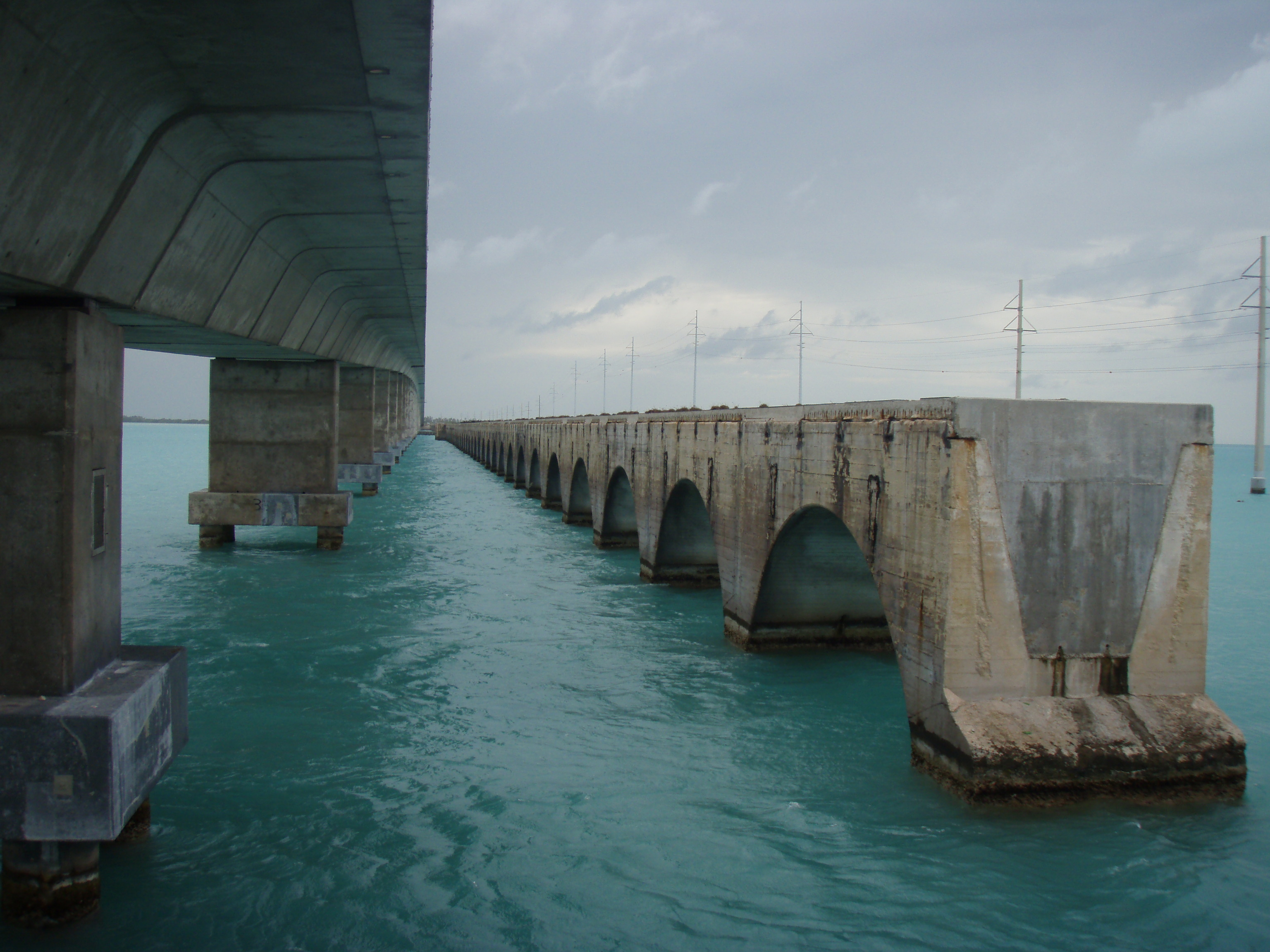 Two bridges on the w:Overseas Highway within the Florida Keys. The bridge on the left is the modern highway bridge, while the bridge on the right is the original bridge built by the Florida East Coast Railway, retrofitted to automobile traffic after 1935, and later closed.