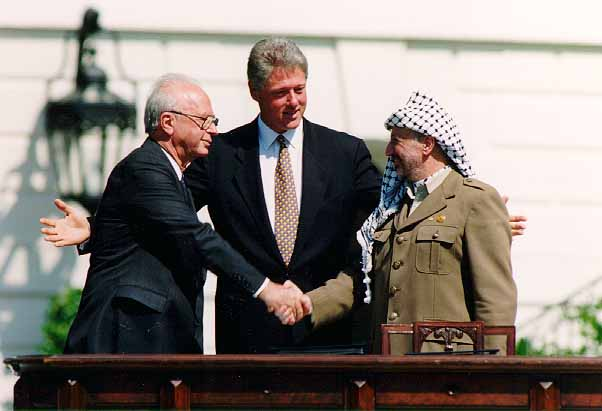 Rabin and Arafat shake hands in front of President Clinton.