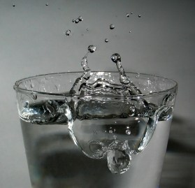The impact of a drop of water in a full glass of water