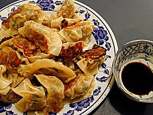 A plate of fried dumplings (guotie), and dippi...