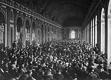 Photographie de la très longue et large Galerie des glaces où une foule innombrable se tient debout autour de personnes assises en groupe sur des chaises.