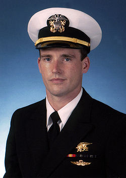 Color photograph of Michael Murphy, a U.S. Navy officer, wearing a military dress uniform. There is a blue background behind him and he is wearing a gold Navy Seal Trident, two blue and green striped ribbons, one red and yellow striped ribbon and gold parachute insignia wings below the ribbons.