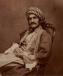 Sepia photograph of a man in 19th century Middle Eastern dress, with a large moustache, reclining in a chair with his hands crossed across his lap