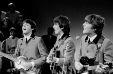 Paul McCartney, George Harrison, and John Lennon playing guitars and wearing matching grey suits.
