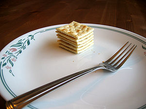 English: Six saltines and a fork on a large plate
