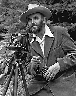 A photo of a bearded Ansel Adams with a camera on a tripod and a light meter in his hand.  Adams is wearing a dark jacket and a white shirt, and the open shirt collar is spread over the lapel of his jacket.  He is holding a cable release for the camera, and there is a rocky hillside behind him.  The photo was taken by J. Malcolm Greany, probably in 1947.