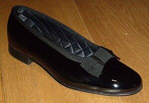 English: A patent leather men's court shoe (pu...