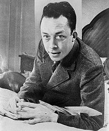 Albert Camus, gagnant de prix Nobel, portrait en buste, posé au bureau, faisant face à gauche, cigarette de tabagisme.jpg