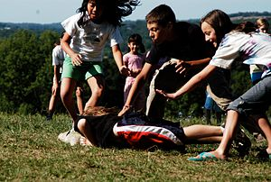 English: Children playing a variant of tag. In...