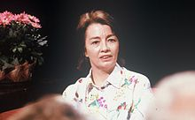 A photograph of a woman with shoulder-length brown hair facing the viewer and looking slightly to the right while wearing a white shirt with a floral print