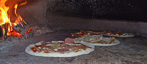 English: A wood-burning pizza oven baking pizz...