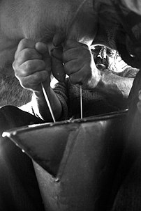 Milking a cow's udders by hand.