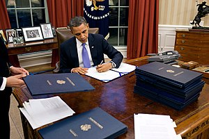 President Barack Obama signs legislation in th...