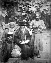 A sepia photograph shows three elderly Jewish men sporting beards and holding open books, posing for the camera. Against a backdrop of leafy vegetation, the man in the centre sits, wearing a black hat and caftan, while the two others stand, wearing lighter clothes and turbans.