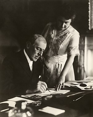 President Woodrow Wilson, seated at desk with ...