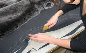 Furrier is cutting leather for a bluefox coat ...