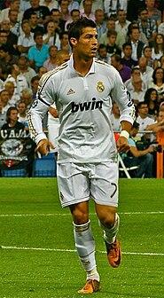 Un homme en chemise blanche et un short regardant vers le haut.