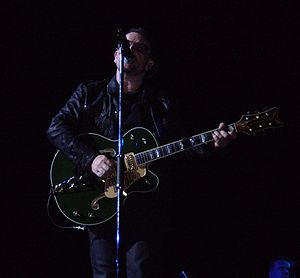An image of Bono playing guitar during a perfo...