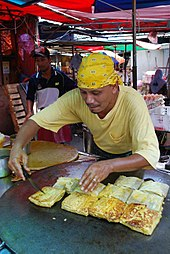 A cook making Murtabak, a type of pancake, in an outdoor stall. He is pictured leaning over his custom-made flattened wok filled with pieces of murtabak.