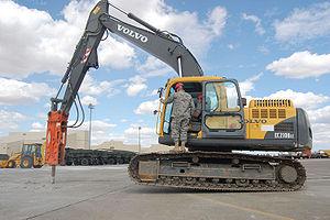 An excavator-mounted hydraulic jackhammer bein...