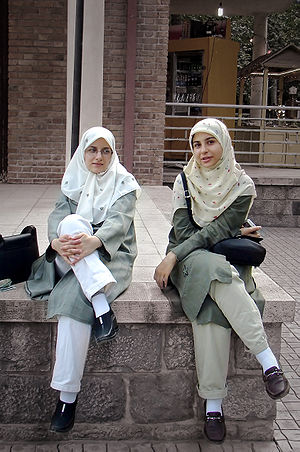 Two seated women in Iran wearing proscribed hi...