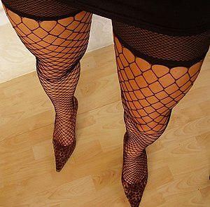 Person wearing fishnet stockings and high heels.