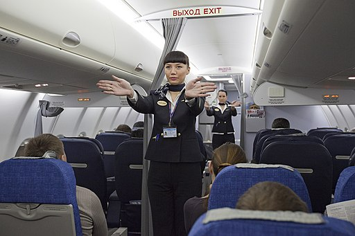 Flight attendants performing a pre-flight safety demonstration on an Aeroflot Sukhoi Superjet