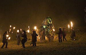 Fire-bearers circle figures of The Green Man f...