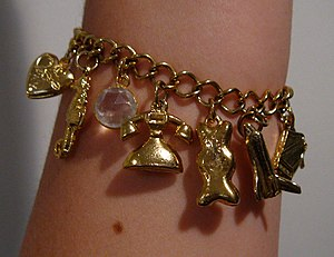 English: A gold charm bracelet worn on the arm...