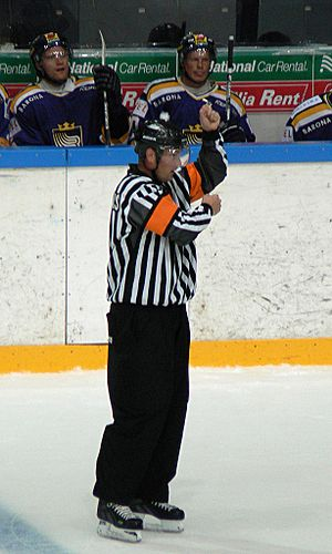 An ice hockey referee signals a penalty for hi...